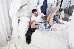Неимоверно милая пара обнимая в кровати дома и иметь потеху стоковое изображение
