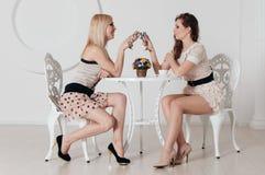 2 неимоверных девушки сидят на таблице Стоковое Фото