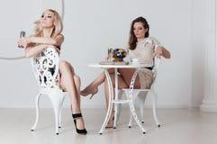2 неимоверных девушки сидят на таблице Стоковые Фотографии RF