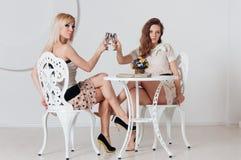 2 неимоверных девушки сидят на таблице Стоковое Изображение