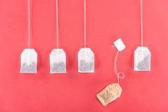4 неиспользованных пакетика чая и один использовали пакетик чая изолированный на красном цвете стоковые изображения rf