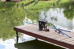 Неиспользованные рыболовные удочки на деревянной пристани Штанги полагаются против st стоковое изображение rf