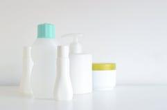 Некоторые бутылки косметики, дух и лосьона на белой таблице Стоковые Изображения