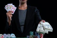 Некоторые деньги и сердца одевают прямой поток в женских руках Стоковое фото RF