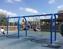 Некоторые дети играя на спортивной площадке Стоковое Фото