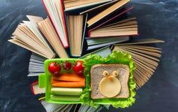 Некоторые книги с коробкой lunce на столе над классн классным Стоковые Изображения