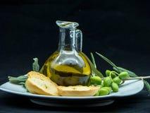Некоторые оливки и опарник вполне масла и ветви оливкового дерева дальше Стоковые Изображения