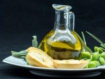 Некоторые оливки и опарник вполне масла и ветви оливкового дерева дальше Стоковые Фотографии RF