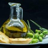 Некоторые оливки и опарник вполне масла и ветви оливкового дерева дальше Стоковое Изображение
