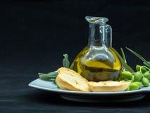 Некоторые оливки и опарник вполне масла и ветви оливкового дерева дальше Стоковые Изображения RF