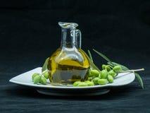 Некоторые оливки и опарник вполне масла и ветви оливкового дерева дальше Стоковое фото RF