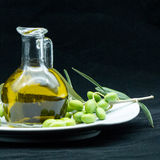 Некоторые оливки и опарник вполне масла и ветви оливкового дерева дальше Стоковое Изображение RF