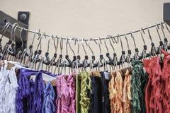 Некоторые повешенные красочные одежды в магазине стоковое изображение rf