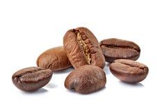 Некоторые свежие зажаренные в духовке кофейные зерна на белизне Стоковое Изображение RF