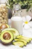 Некоторые части отрезанного авокадоа на таблице и бутылке молока и maccadamia Стоковая Фотография