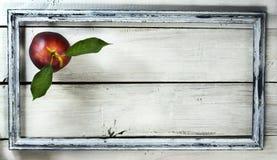 Нектарин в старой рамке на белой деревянной предпосылке Стоковые Фото