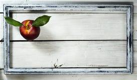 Нектарин в старой рамке на белой деревянной предпосылке Стоковое фото RF