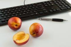 Нектарин на таблице офиса и компьютере на предпосылке Стоковая Фотография