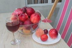 Нектарин, персики и сливы с падениями воды на деревянной таблице стеклянное красное вино Стоковое Фото