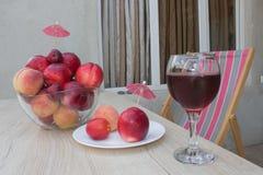 Нектарин, персики и сливы с падениями воды на деревянной таблице стеклянное красное вино Стоковая Фотография