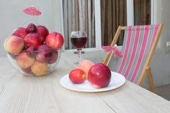 Нектарин, персики и сливы с падениями воды на деревянной таблице стеклянное красное вино Стоковые Фотографии RF