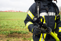 Немецкий пожарный с шлангом воды в действии стоковое фото rf
