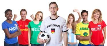 Немецкий сторонник футбола с шариком и вентиляторы от других стран стоковые фотографии rf