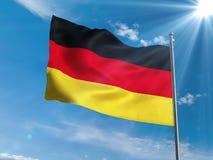 Немецкий флаг развевая в голубом небе с солнцем Стоковое Изображение RF