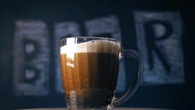 """Немецкое пиво льет в стекло на черной предпосылке с надписью: """"пиво """" видеоматериал"""