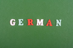 Немецкое слово на зеленой предпосылке составленной от писем красочного блока алфавита abc деревянных, космосе экземпляра для текс Стоковое Фото