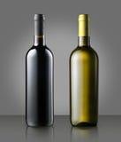 Немеченые бутылки красного и белого вина на сером цвете Стоковое фото RF