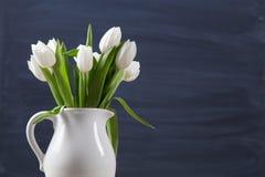 Немногие цветки тюльпанов на темной поверхности chalcboard Букет на предпосылке конспекта нерезкости с космосом экземпляра стоковое фото