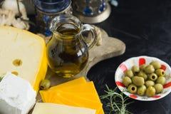 Немногий различный вид сыров с оливками бумагой и оливковым маслом на черной доске в кухне стоковое фото
