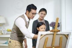 Немногое азиатская девушка делая картину с родителями наблюдая и помогая стоковые изображения rf