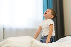 Немногое азиатский мальчик плача горько кризис 3 лет, истеричность детей дома мальчик в белом скандале футболки стоковое фото rf