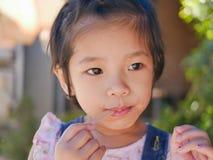 Немногое азиатский ребенок наслаждается положить ручку в ее рот даже после она имеет eatten все мороженое стоковое изображение