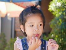 Немногое азиатский ребенок наслаждается положить ручку в ее рот даже после она имеет eatten все мороженое стоковое фото