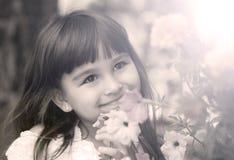 Немногое белая девушка со счастливой улыбкой около цветков, солнечным днем стоковая фотография