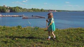 Немногое белокурая девушка надувает большие пузыри мыла против фона морского побережья видеоматериал