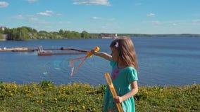 Немногое белокурая девушка надувает большие пузыри мыла против фона морского побережья акции видеоматериалы