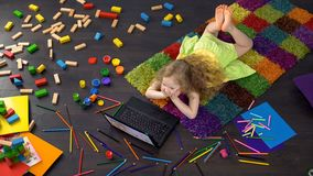 Немногое белокурая курчавая девушка наблюдая воспитательный мультфильм на ноутбуке, уча номера стоковые фото