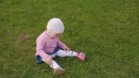Немногое двухлетняя красивая девушка в шляпе сидит на зеленой траве н видеоматериал