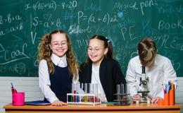 Немногое дети на лаборатории Микроскоп химии студенты делают эксперименты по биологии с микроскопом Микроскоп лаборатории стоковое фото rf