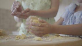 Немногое дочь при исследовании ее матери свертывая вне и формируя тесто для плюшек r сток-видео