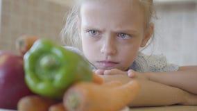 Немногое дочь сердито смотря плиту с овощами потому что она не хочет есть их r видеоматериал