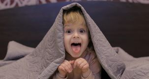 Немногое жизнерадостная девушка прячет под одеялом и ТВ смотреть Концепция сна детей стоковые изображения
