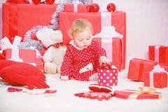 Немногое игра ребенка около кучи подарочных коробок Праздник семьи Подарки для рождества ребенка первого Деятельности при рождест стоковые фото
