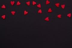 Немногое из маленьких красных сердец na górze черной предпосылки Стоковое Изображение RF