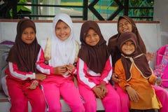 Немногое индонезийские девушки детей в hijabs ждет школьный автобус на автобусной остановке стоковое фото