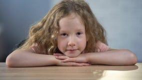 Немногое кавказская девушка сидя самостоятельно на таблице и смотря в камеру, детский дом стоковое изображение